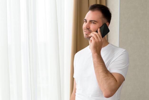 Hübscher kaukasischer mann, der durch fenster im hotel schaut, während auf smartphone spricht