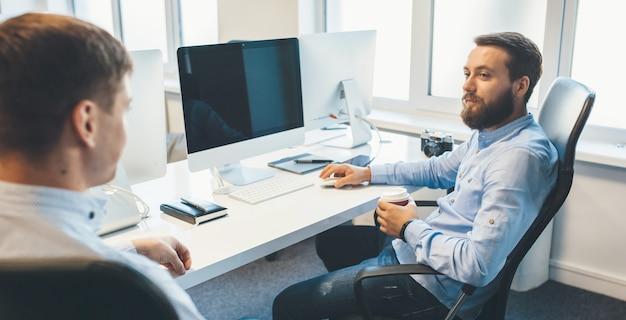 Hübscher kaukasischer mann, der einen kaffee trinkt, führt einen dialog mit seinem arbeitskollegen im büro.