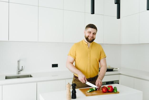 Hübscher kaukasischer mann im gelben schneiden von gemüse für mahlzeit oder salat in der modernen weißen küche lächelnd