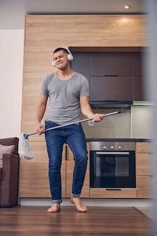 Hübscher kaukasischer mann in weißen kopfhörern, der mit wischstab steht und beim bodenwaschen singt