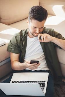 Hübscher kaukasischer mann mit bart, der auf handy plaudert und einen laptop hält, während er auf dem boden sitzt