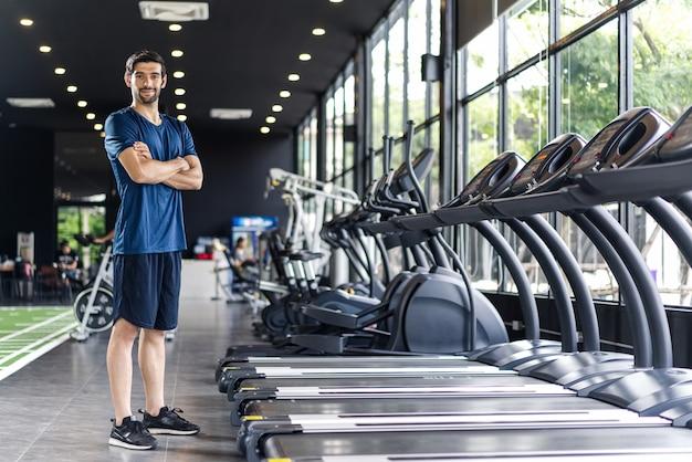 Hübscher kaukasischer mann mit bart in der blauen farbsportkleidung, welche die arme in der turnhalle oder im fitness-club steht und kreuzt.