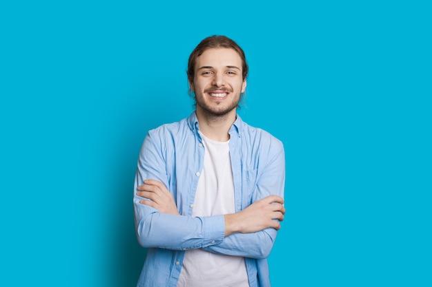 Hübscher kaukasischer mann mit bart und langen haaren posiert mit gekreuzten händen
