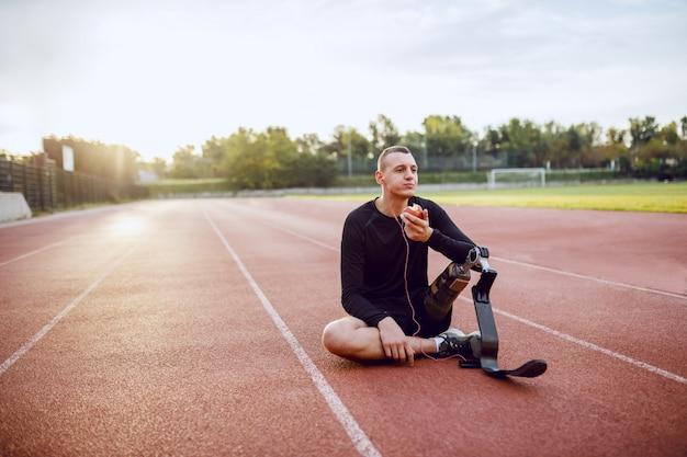 Hübscher kaukasischer sportlicher behinderter junger mann in sportbekleidung und mit künstlichem bein, das auf rennstrecke sitzt, musik hört und apfel isst.