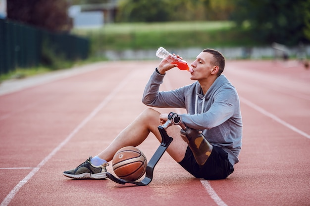 Hübscher kaukasischer sportlicher behinderter mann in der sportbekleidung, die auf rennstrecke sitzt und erfrischung trinkt. zwischen den beinen ist basketball.