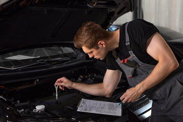 Hübscher kaukasischer typ macht sich notizen, während er motorhaube des autos repariert