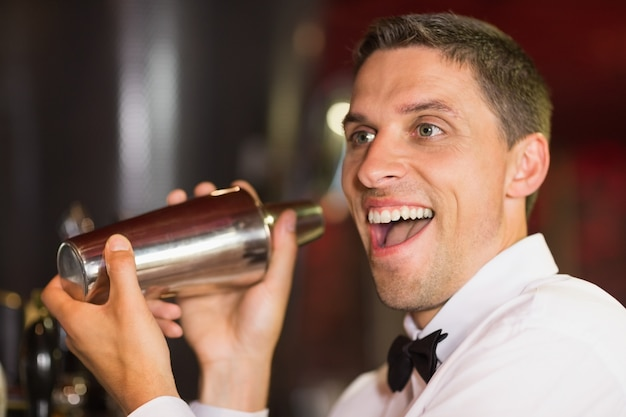Hübscher kellner, der an der kamera macht ein cocktail lächelt
