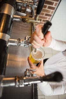 Hübscher kellner, der ein halbes liter bier gießt