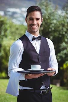 Hübscher kellner, der einen behälter mit tasse kaffee hält