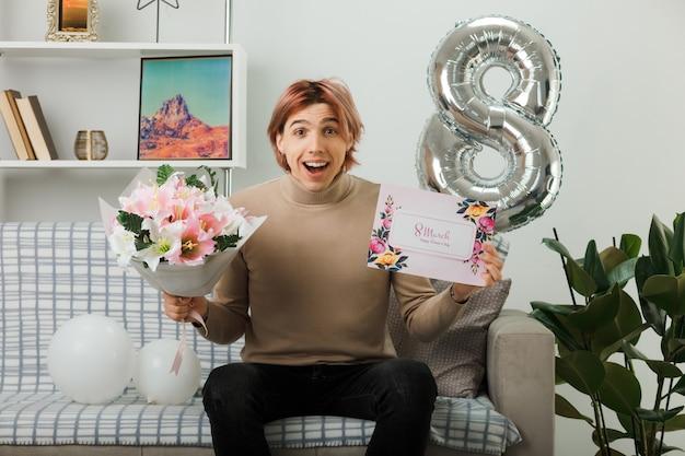 Hübscher kerl am glücklichen frauentag, der blumenstrauß mit postkarte hält, die auf sofa im wohnzimmer sitzt