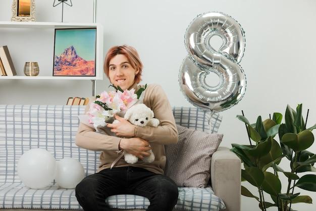 Hübscher kerl am glücklichen frauentag, der blumenstrauß mit teddybär hält, der auf sofa im wohnzimmer sitzt