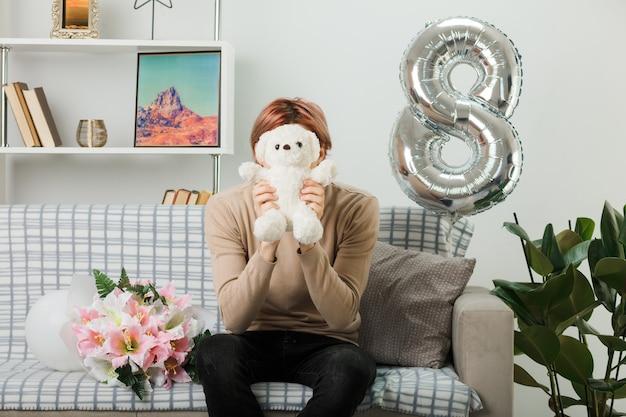 Hübscher kerl am glücklichen frauentag, der das gesicht mit dem teddybären hält und bedeckt, der auf dem sofa im wohnzimmer sitzt