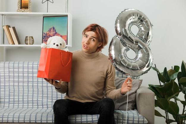 Hübscher kerl am glücklichen frauentag, der den ballon nummer acht mit der geschenktüte hält, die auf dem sofa im wohnzimmer sitzt