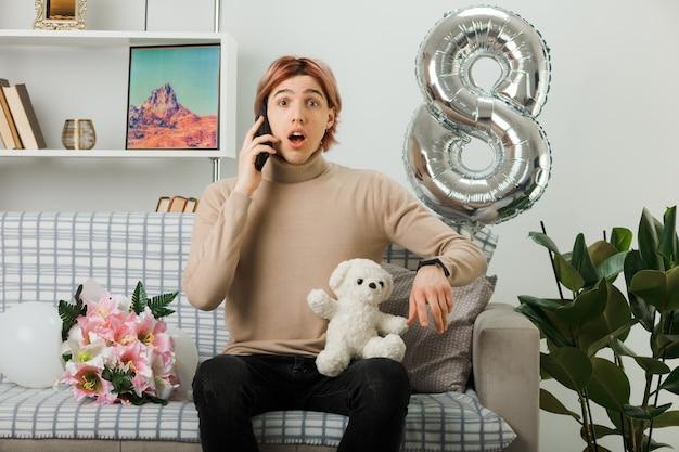 Hübscher kerl am glücklichen frauentag, der teddybären hält, spricht am telefon, das auf sofa im wohnzimmer sitzt