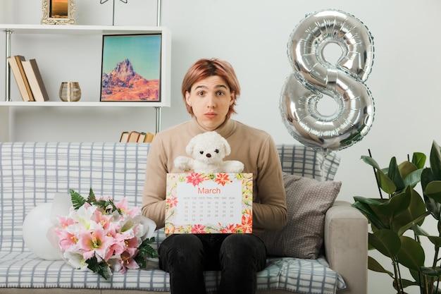 Hübscher kerl am glücklichen frauentag, der teddybären mit kalender hält, der auf sofa im wohnzimmer sitzt