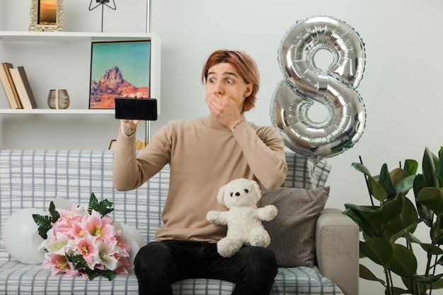 Hübscher kerl am glücklichen frauentag, der teddybären mit telefon hält, der auf sofa im wohnzimmer sitzt