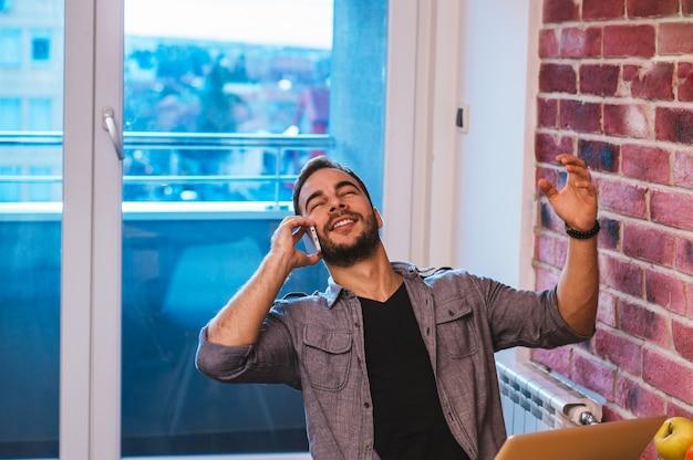 Hübscher kerl, der am telefon, gute nachrichten hörend spricht