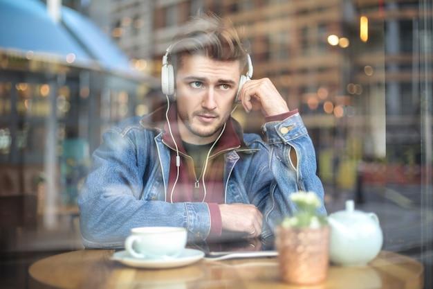 Hübscher kerl, der auf dem tisch einer kaffeestube, hörende musik mit kopfhörern sitzt
