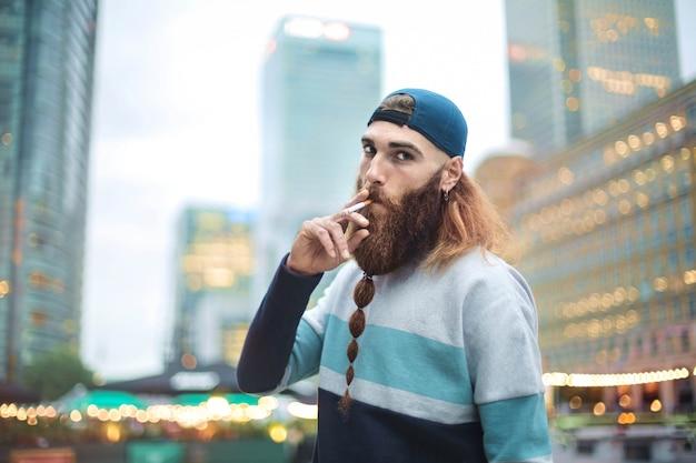 Hübscher kerl, der auf der straße steht und eine zigarette raucht