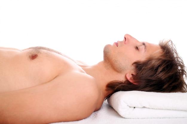 Hübscher kerl, der bei massagesitzung sich entspannt
