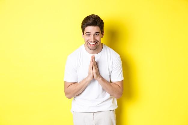 Hübscher kerl, der danke sagt, sich verbeugt und hände in namaste geste hält, dankbarkeit ausdrückt, über gelbem hintergrund stehend.