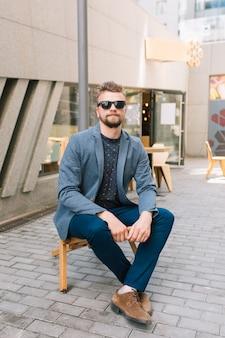 Hübscher kerl, der draußen auf stuhl sitzt