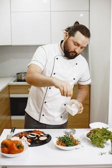 Hübscher kerl, der in der küche zu hause steht.