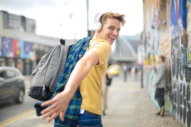 Hübscher kerl, der in die straße während hörende musik mit kopfhörern läuft