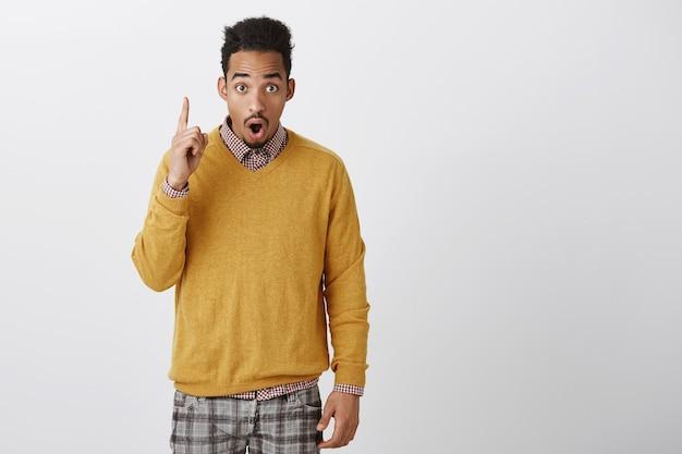 Hübscher kerl, der kiefer von unglaublichen nachrichten fallen lässt. porträt des emotionalen jungen afroamerikanischen mannes mit afro-frisur im trendigen gelben pullover, der nach oben zeigt und mit schock und wunder über graue wand schaut