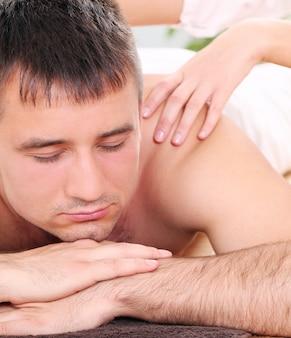 Hübscher kerl, der massagetherapie genießt