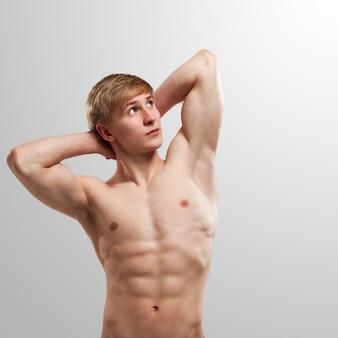 Hübscher kerl, der mit dem nackten torso aufwirft