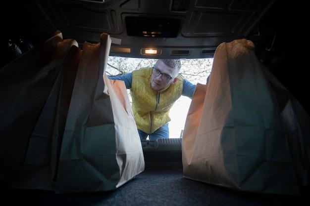 Hübscher kerl, der papiertüten in autokofferraum nach supermarkteinkauf setzt
