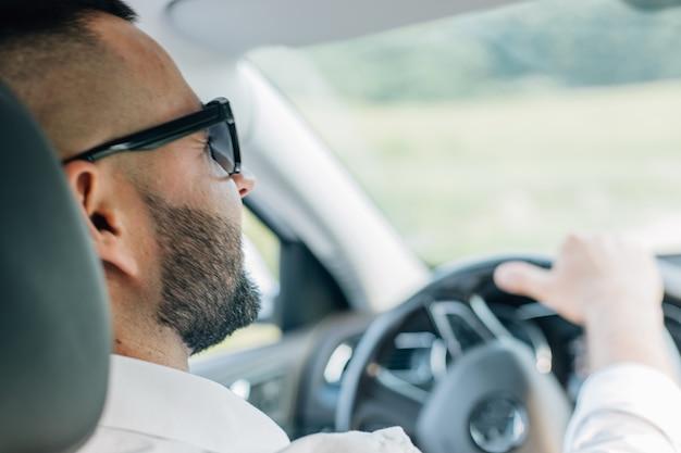 Hübscher kerl, der sein auto fährt. bärtiger mann von stil und status. junger mann in einem luxusauto.