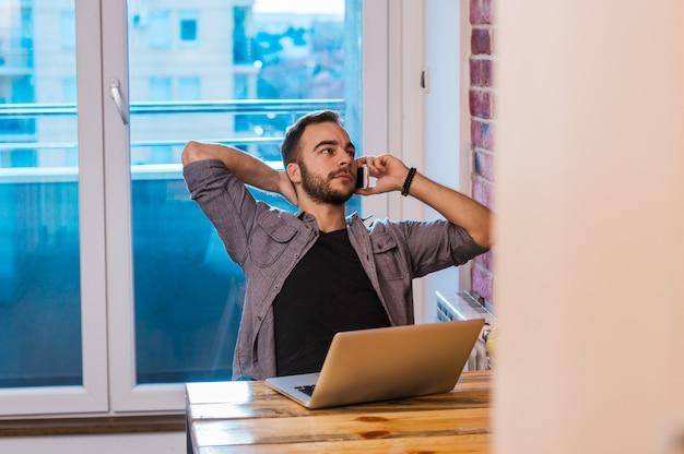 Hübscher kerl, der über smartphone beim arbeiten im büro spricht.
