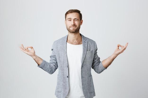 Hübscher kerl, der versucht zu meditieren und während der yoga-sitzung späht