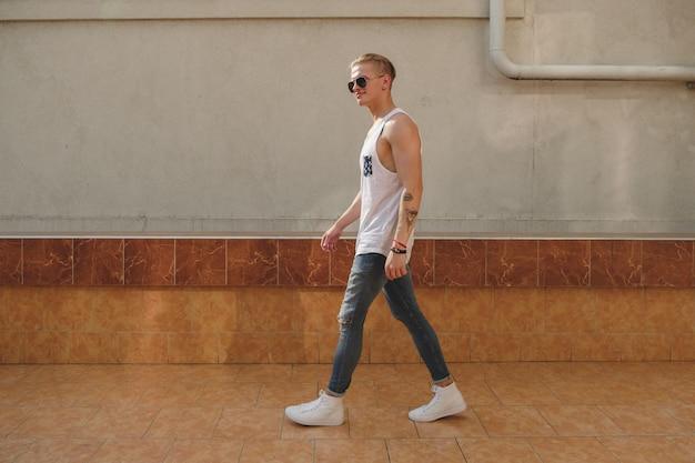 Hübscher kerl des blonden mannes des hippies im stilvollen sommer kleidet in der straße
