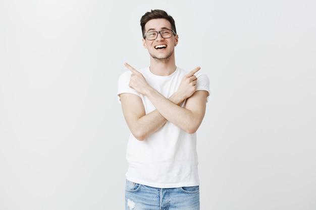 Hübscher kerl in brille zeigt mit den fingern zur seite, braucht hilfe bei der auswahl