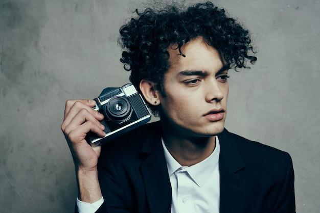 Hübscher kerl in einem anzug mit einem kamerastunden-modell für lockiges haar