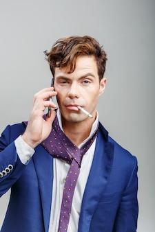 Hübscher kerl in einem anzug mit einer zigarette und am telefon sprechen