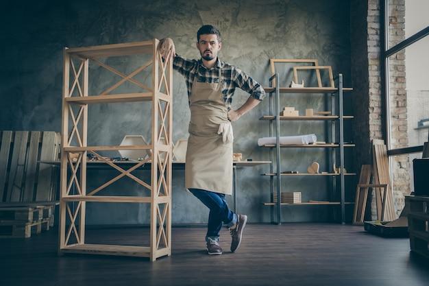 Hübscher kerl in voller länge, der gerade gemachtes bücherregal handgemachtes hölzernes design zeigt, das eigenen geschäftsservice holzwerkstatt drinnen wirbt
