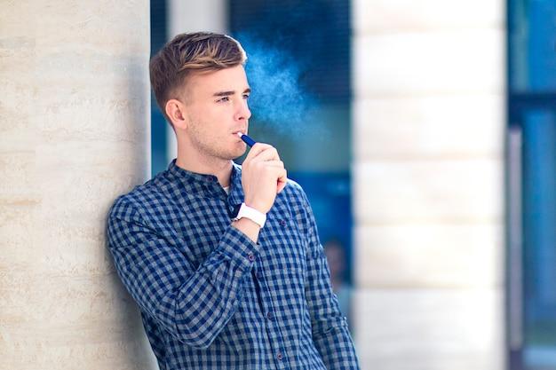 Hübscher kerl, junger mann raucht, erhitzt tabakprodukt, junge mit einer neuen e-zigarette. alternative zum rauchen.