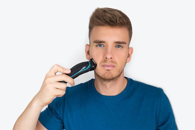 Hübscher kerl, junger schöner mann, der sich mit einem elektrorasierer rasiert, seinen bart schneidet, für gesichtsbehaarung sorgt, lokalisiert auf weiß. schönheit, männer körperpflege. haarspange