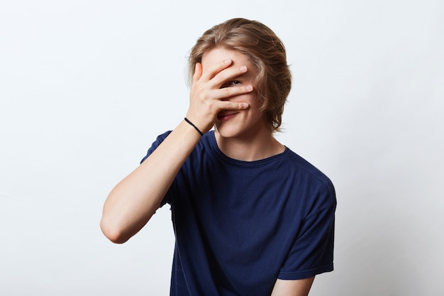 Hübscher kerl mit attraktivem aussehen, versteckt sein gesicht mit der hand, schaut durch die finger, hat schüchternen ausdruck. junger hipster-typ, der nicht fotografiert werden möchte und sein gesicht mit der hand bedeckt