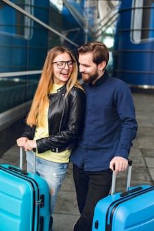 Hübscher kerl mit bart steht mit hübschem mädchen mit langen haaren draußen im flughafen. sie müssen koffer in der nähe haben. sie umarmen sich und sehen glücklich aus.