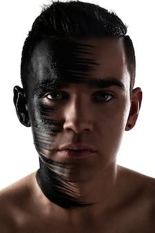 Hübscher kerl mit künstlerischem schwarzem schatten auf seinem gesicht
