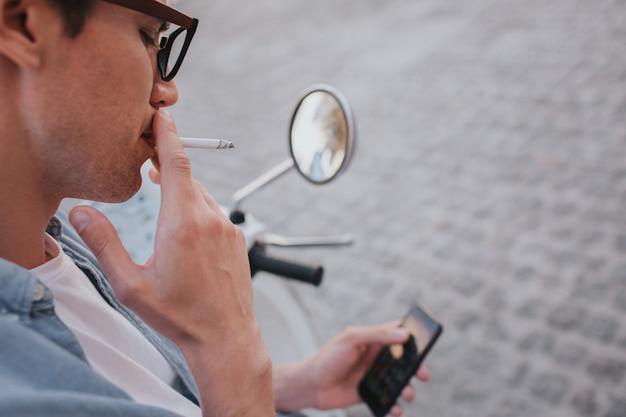 Hübscher kerl sitzt auf motorrad und hält telefon in der hand beim rauchen einer zigarette