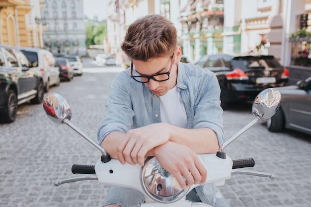Hübscher kerl sitzt auf motorrad und schaut unten