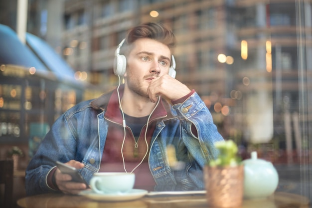 Hübscher kerl sitzt in einer bar und hört etwas mit kopfhörern