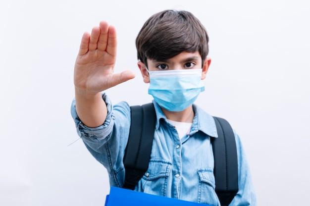 Hübscher kinderjunge student mit rucksack und maske, die bücher auf lokalisiertem weißem hintergrund mit offener hand halten stoppschild halten