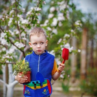 Hübscher kleiner blonder junge, der blumen im garten oder in der farm am frühlingstag pflanzt und im garten arbeitet